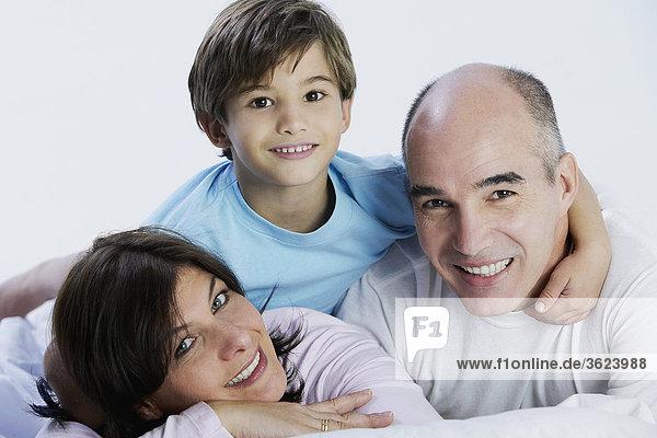 Porträt eines jungen und seine Eltern auf dem Bett liegend