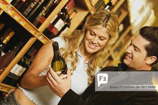 Nahaufnahme eines jungen Paares hält eine Flasche Weine in einem Supermarkt