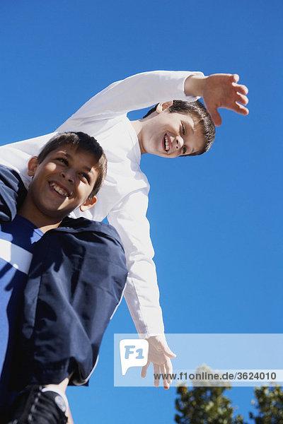 Untersicht of ein Teenager mit seinem Bruder auf seinen Schultern