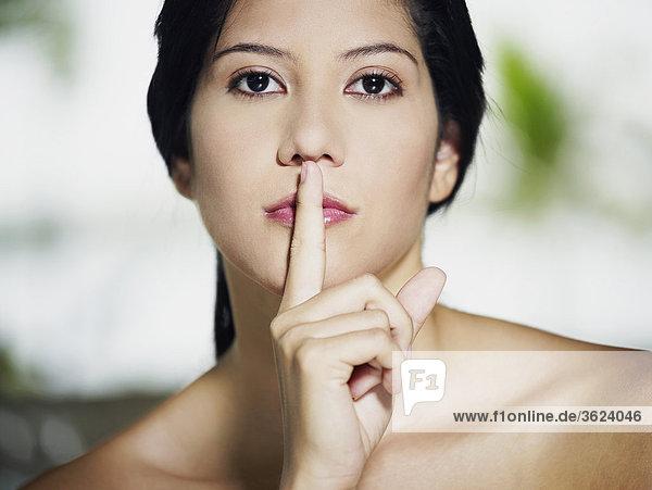 Portrait einer jungen Frau mit ihrem Finger auf ihre Lippen
