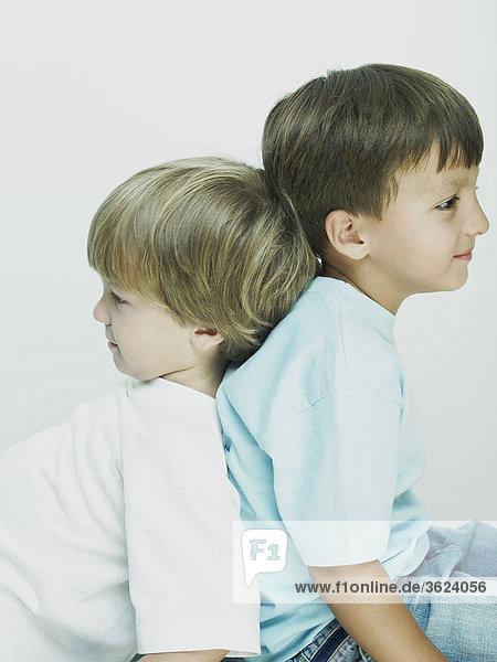Seitenprofil zweier jungen Rücken an Rücken sitzen