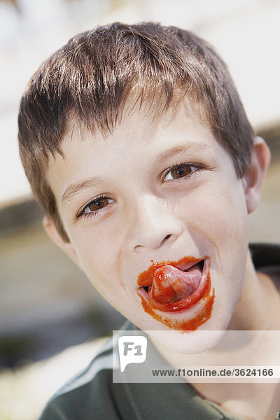 Portrait of a boy licking ketchup from his lips