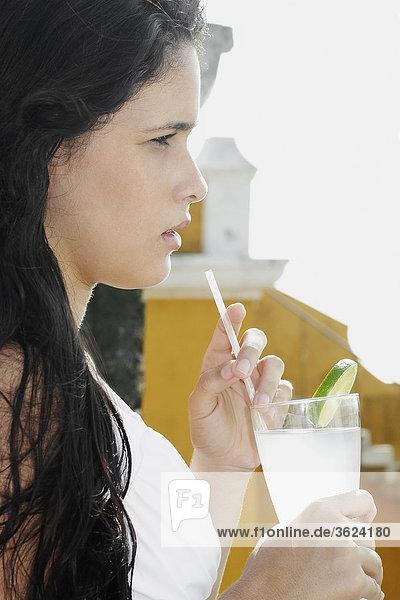 Seitenansicht einer jungen Frau mit einem Glas Limonade