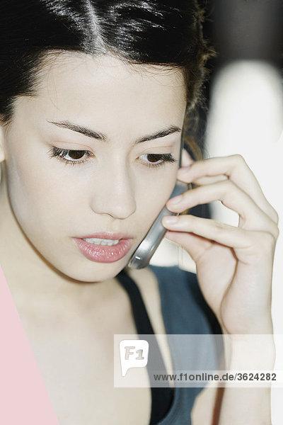 Nahaufnahme einer jungen Frau mit einem Mobiltelefon