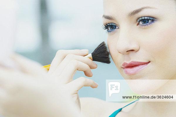 Nahaufnahme einer jungen Frau mit einem Make-up-Pinsel
