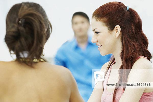 Nahaufnahme der zwei junge Frauen mit einem jungen Mann im Hintergrund