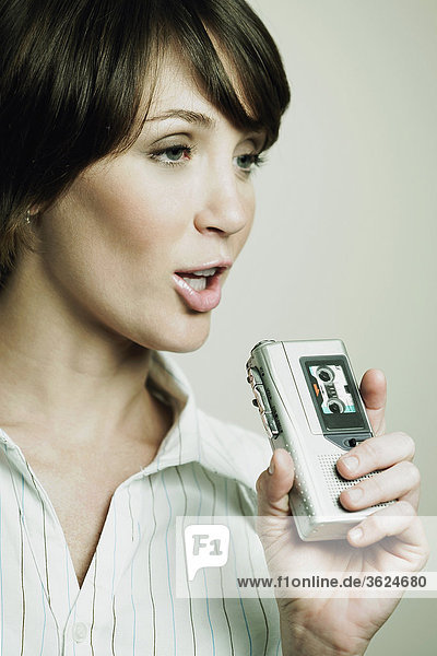 Close-up of a young woman looking away and holding a tape recorder