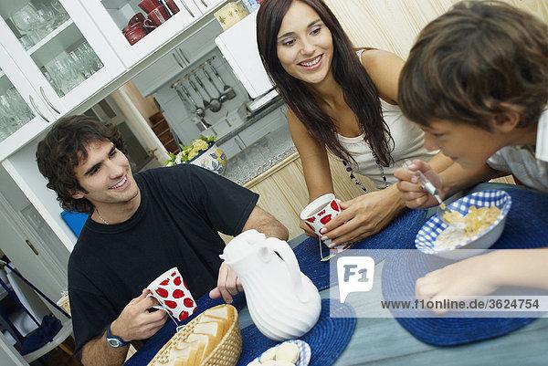 Junges paar lächelnd mit ihrem Sohn bei einem Esstisch