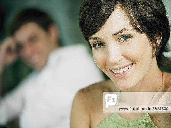 Portrait einer jungen Frau lächelnd mit einem jungen Mann im Hintergrund