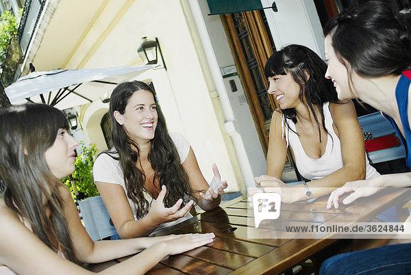 Zwei junge Frauen und zwei Frauen lächelnd und zusammensitzen