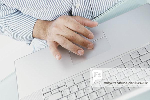 Mitte Schnittansicht eines Mannes auf einem Laptop arbeiten