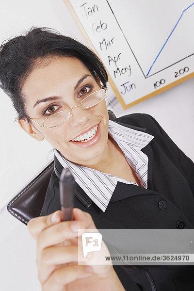 Porträt von geschäftsfrau hält einen Stift und lächelnd