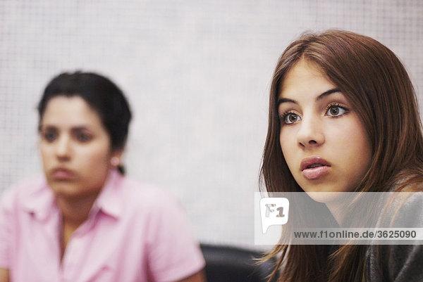 Nahaufnahme einer jungen Frau looking überrascht mit einer anderen jungen Frau im Hintergrund