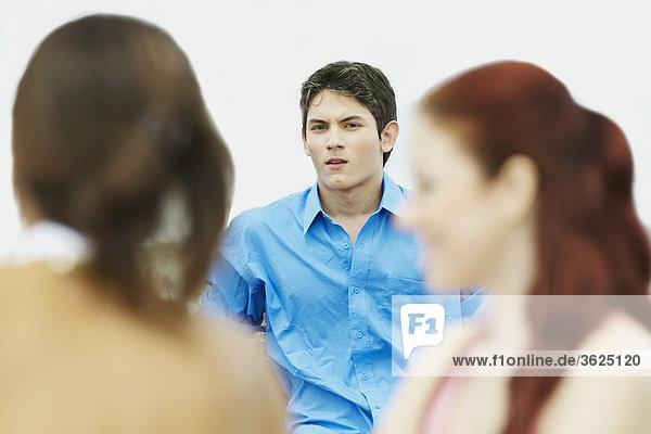 Porträt eines jungen Mannes mit zwei junge Frauen sitzen
