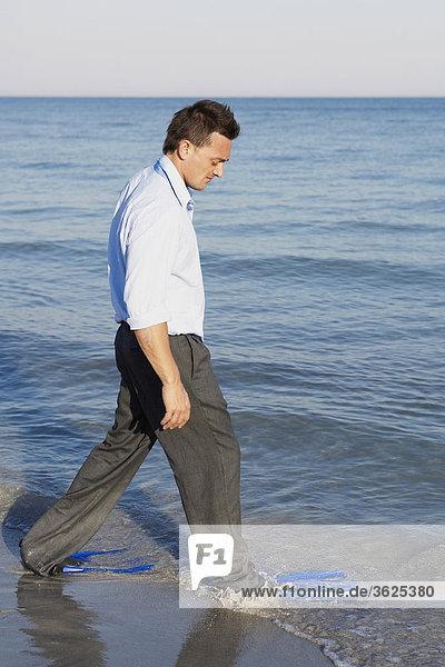 Seitenansicht eines jungen Mannes tragen Flossen und Wandern am Strand