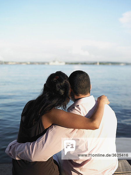 Rückansicht eines jungen Paares sitzen auf eine Pier Arme umeinander