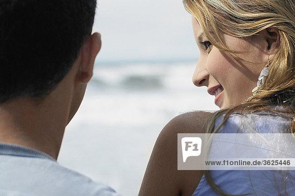 Rückansicht einer jungen Frau und ein Mann am Strand
