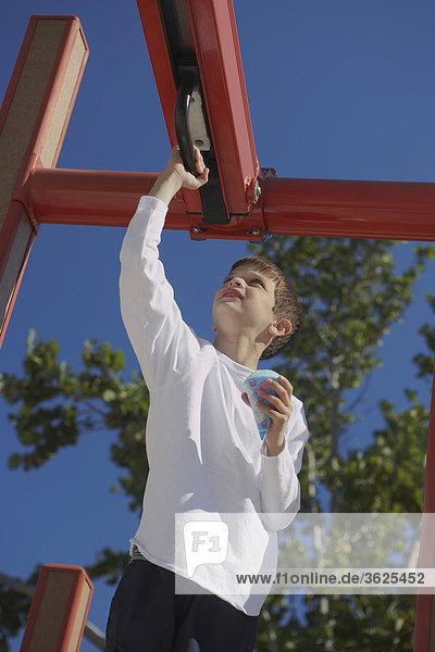 Untersicht eines jungen auf ein Klettergerüst spielen