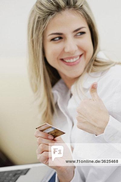 Nahaufnahme der geschäftsfrau hält eine Kreditkarte und zeigt ein Daumen hoch Zeichen