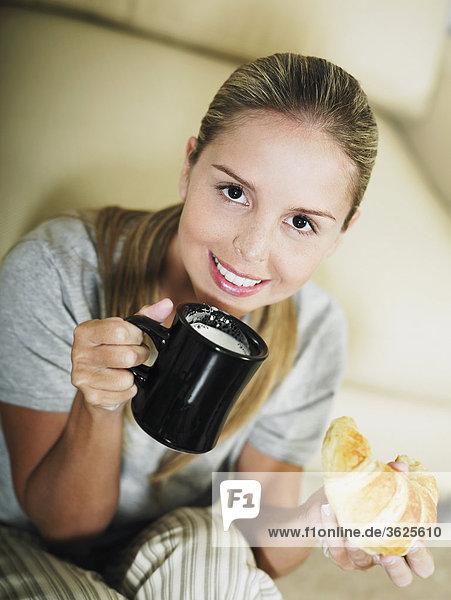 Portrait einer jungen Frau hält eine Kaffeetasse und einem croissant