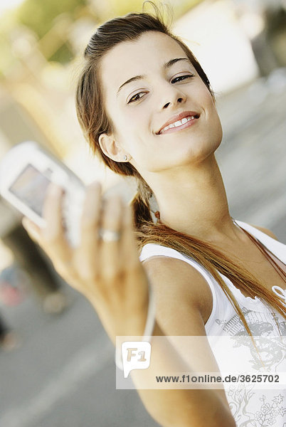 Close-up of a young woman taking a photograph of herself