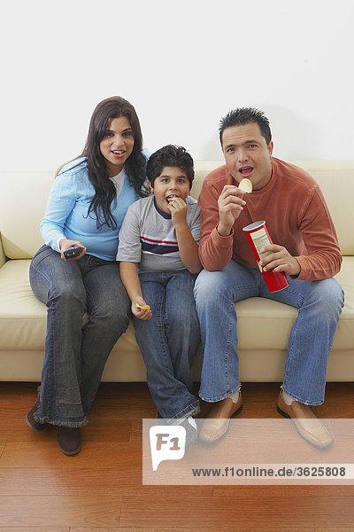 Mitte Erwachsenen Mann und eine junge Frau mit ihrem Sohn auf einer Couch sitzen und Fernsehen