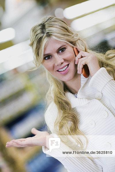 Portrait einer jungen Frau lächelnd und sprechen auf einem Mobiltelefon
