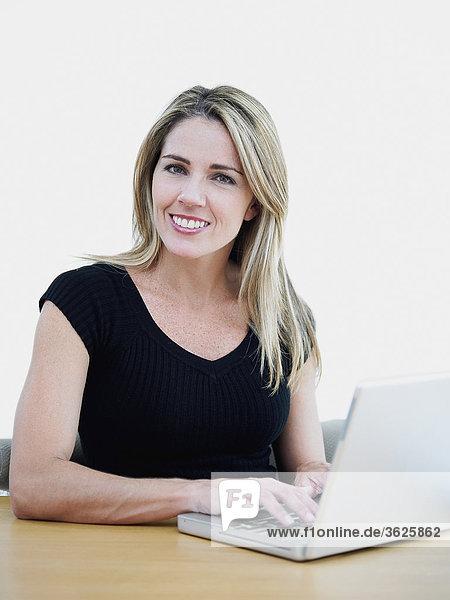 Portrait einer Mitte erwachsen frau mit einem laptop