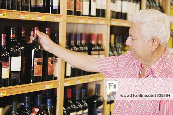 Nahaufnahme ein älterer Mann mit eine Weinflasche in ein Spirituosengeschäft