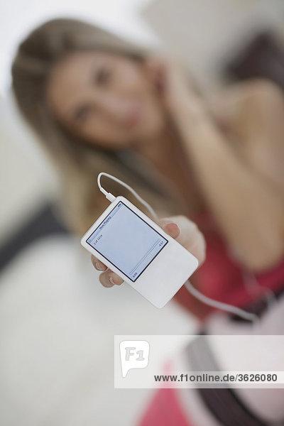 Nahaufnahme einer Mitte erwachsen frau zeigt einen MP3-player