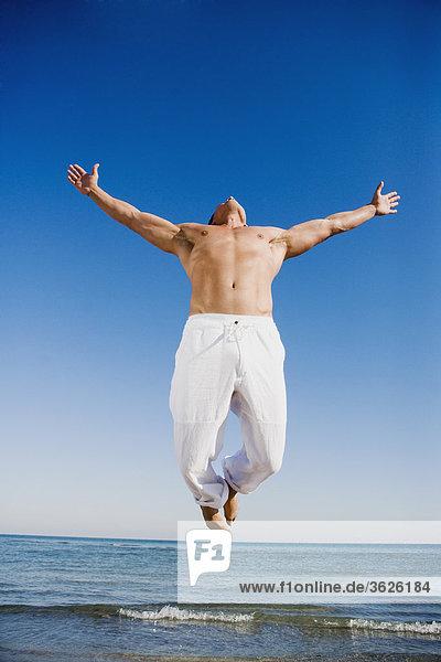 Untersicht eines jungen Mannes mit seine Arme ausbreiten und springen am Strand