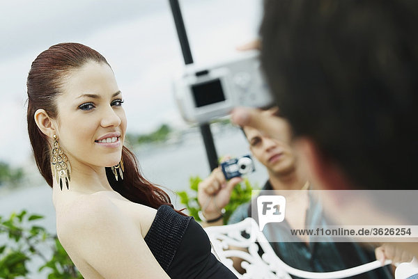 Zwei junge Männer  die ein Bild von einer jungen Frau anwenden-Make-up