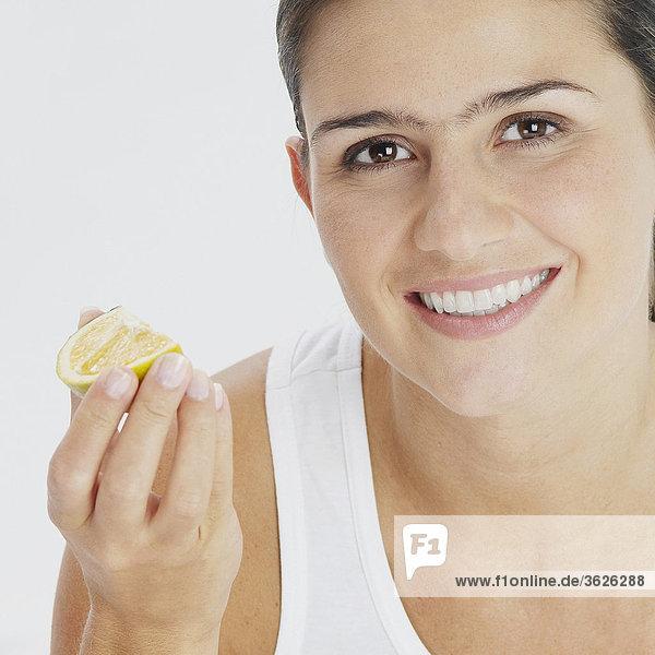 Portrait einer jungen Frau hält eine Scheibe von Kalk und lächelnd