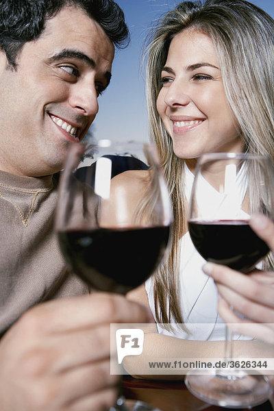 Untersicht von Mitte Erwachsenen Mann und ein Mitte adult Frau hält Gläser Rotwein