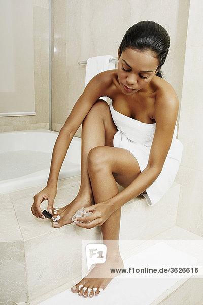 Young woman applying nail polish on her toe nails