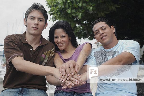 Portrait einer jungen Frau mit zwei junge Männer sitzen und lächelnd