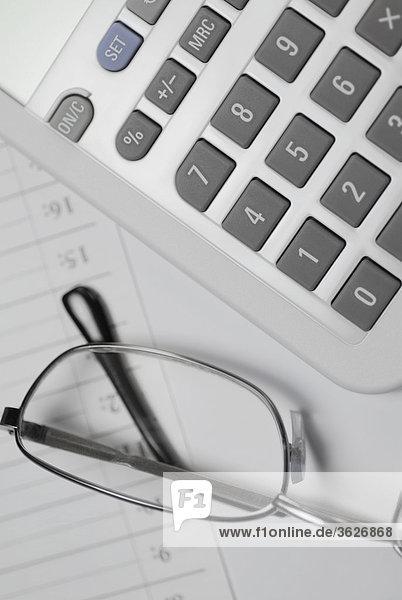 Nahaufnahme Brille mit einem Taschenrechner auf ein Tagebuch