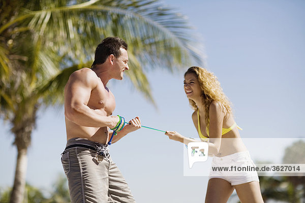 Young couple standing on the beach and pulling a rope