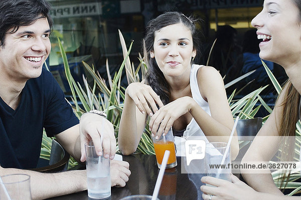 Young man and three young women smiling together in a restaurant