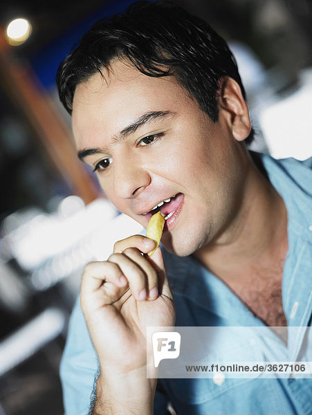 Close-up of a young man eating French fries