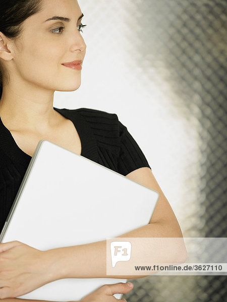 Close-up of a young woman holding a laptop