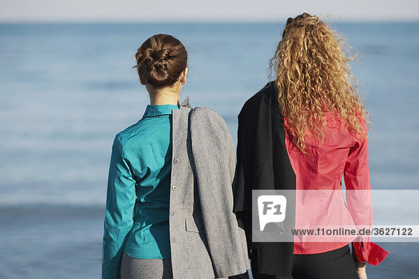 Rear view of two women standing on the beach