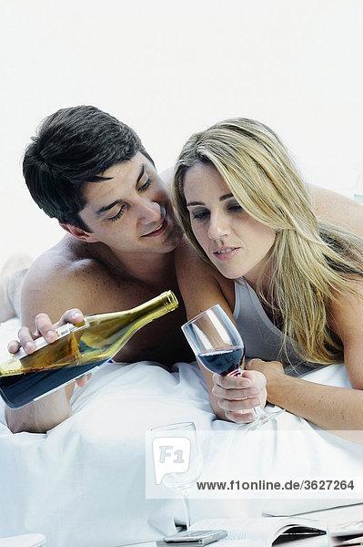 Nahaufnahme ein Mitte adult Paar auf dem Bett liegend und hält eine Flasche und ein Glas Wein