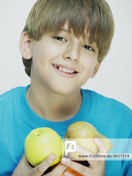 Bildnis eines Knaben hält eine Birne und einen Apfel