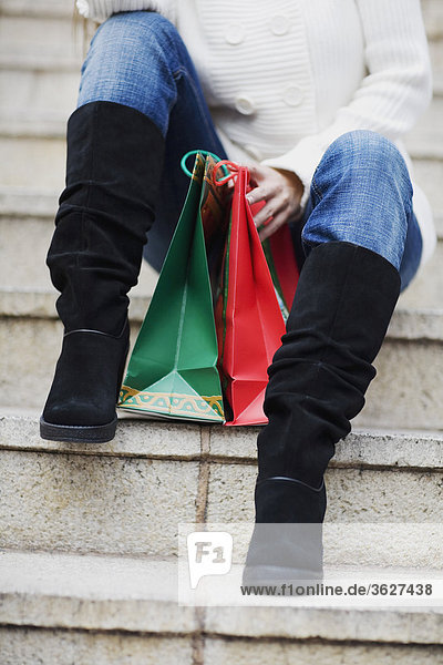 Low section view of a woman sitting on steps with shopping bags