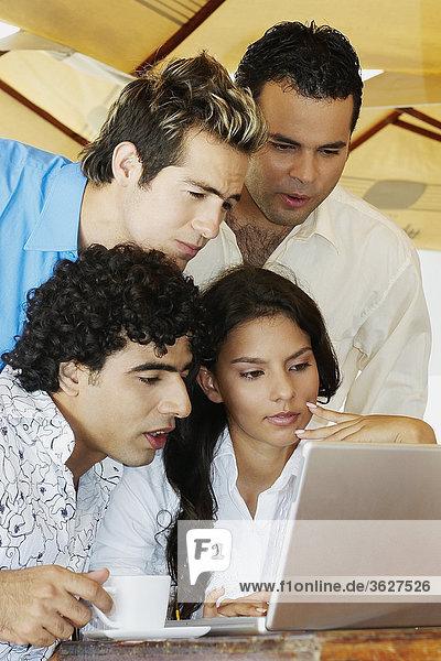 Teenager mit zwei junge Männer und eine junge Frau Blick auf einem laptop