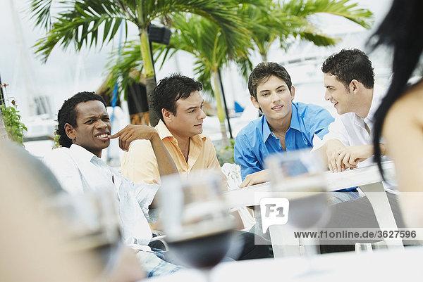Vier junge Männer sitzen in einem restaurant