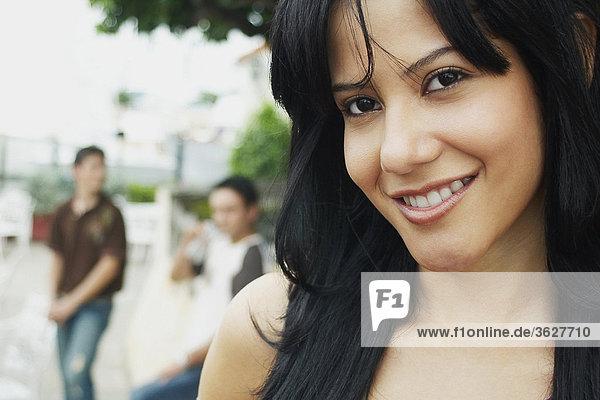 Nahaufnahme einer jungen Frau lächelnd mit drei junge Männer stehen im Hintergrund