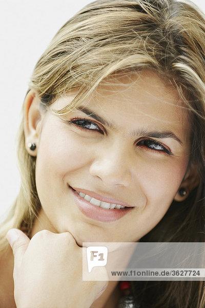 Nahaufnahme einer jungen Frau lächelnd und wegsehen