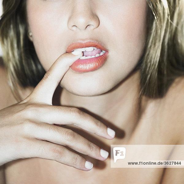 Nahaufnahme einer jungen Frau beißt ihre Nägel